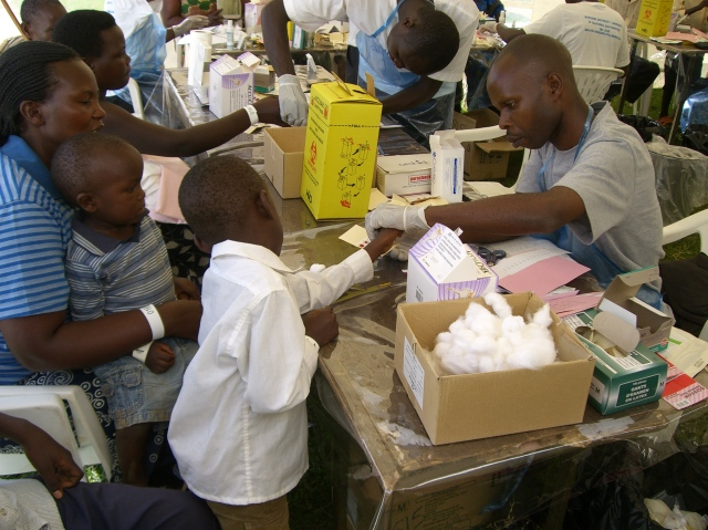 adults and children receiving testing and treatment from a campaign health worker